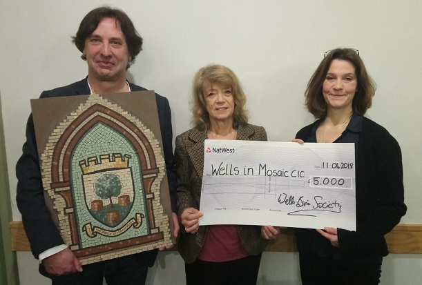 Chris Winter presents a cheque for £5,000 to Ruth Ames-White, while Ian holds an example of mosaic work
